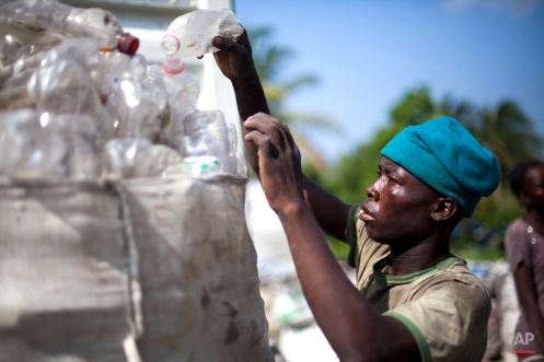In this April 16, 2014 photo, a worker arranges a sack of plastic bottles at a recycling center in Cite Soleil, Port-au-Prince, Haiti. (AP Photo/Dieu Nalio Chery)