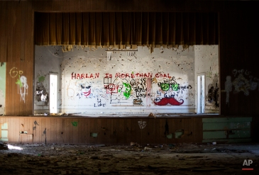"""In this Oct. 17, 2014 photo, a message on the auditorium stage in the abandoned Lynch high School reads """"HARLAN IS MORE THAN COAL,"""" in Lynch, Ky. As Harlan County's population shrunk along with the coal industry, the school closed in 1981 as the county consolidated districts and now sits abandoned up the street from the old mines. (AP Photo/David Goldman)"""