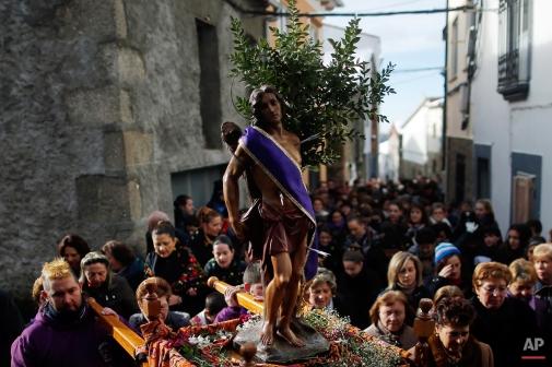 People carry a statue of Saint Sebastian during the Jarramplas Festival in Piornal, Spain, Monday, Jan. 20, 2014. (AP Photo/Andres Kudacki)