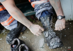 In this Oct. 20, 2014 photo, third generation coal miner Keith Johnson takes off his boots as he arrives home after working the graveyard shift underground in a coal mine in Evarts, Ky. (AP Photo/David Goldman)