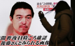 A woman watches a TV news program Wednesday, Jan. 28, 2015 in Tokyo reporting on a video posted on YouTube by jihadists on Tuesday, Jan. 27, that purports to show a still photo of Japanese hostage Kenji Goto holding what appears to be a photo of Jordanian pilot 1st Lt. Mu'ath al-Kaseasbeh. Goto's mother appealed publicly to Japan's leader to save her son after his captors purportedly issued what they said was a final death threat. (AP Photo/Eugene Hoshiko)