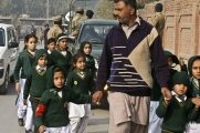 A plainclothes security officer escorts students evacuated from a school as Taliban fighters attack another school nearby in Peshawar, Pakistan, Tuesday, Dec. 16, 2014. (AP Photo/Mohammad Sajjad)