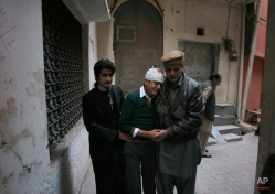The uncle and cousin of injured student Mohammad Baqair, center, comfort him as he mourns the death of his mother who was a teacher at the school which was attacked by Taliban, in Peshawar, Pakistan, Tuesday, Dec. 16, 2014. (AP Photo/Mohammad Sajjad)