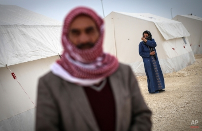 Syrian refugees who fled violence in and around the Syrian city of Ayn al-Arab or Kobani walk in a camp recently opened by Turkey, in the border town of Suruc, Turkey, Friday, Jan. 30, 2015. The 35,000 capacity camp is the largest refugee camp in Turkey. (AP Photo/Emrah Gurel)
