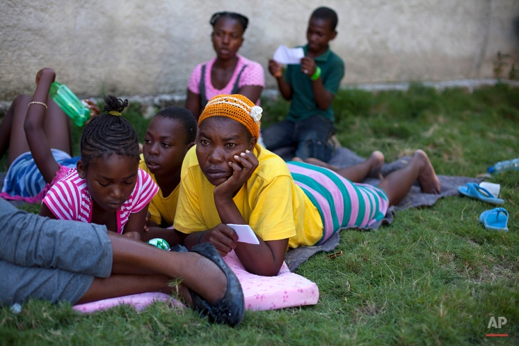 Flerillia Similien, 41, from Haiti, lies on the ground with her children who were born in the Dominican Republic, Anolin Similien, 11, center, and Ketleine Jeune, 13, left, at a shelter after they were deported by Dominican Republic authorities to Croix-des-Bouquets, Haiti, Monday, Nov. 25, 2013. (AP Photo/Dieu Nalio Chery)