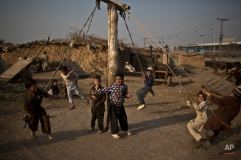 Boys play a fighting game on an improvised swing in a slum that hosts Afghan refugees and internally displaced Pakistanis from tribal areas on the outskirts of Islamabad, Pakistan, Friday, Jan. 9, 2015. (AP Photo/Muhammed Muheisen)