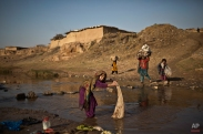 Afghan refugee Fatima Wakeel, 7, washes her laundry in a polluted stream on the outskirts of Islamabad, Pakistan, Wednesday, Jan. 14, 2015. (AP Photo/Muhammed Muheisen)