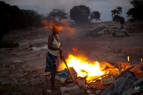 Servinia Dantesque, 44, burns the rest of her tent as she is evicted from the Petion Ville Golf Club, a camp for displaced people of the 2010 earthquake, in Port-au-Prince, Haiti, Wednesday Jan. 22, 2014. (AP Photo/Dieu Nalio Chery)