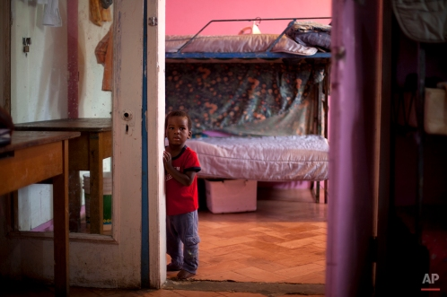 In this Nov. 13, 2013 photo, a young boy stands in his room in the U.S.-based Church of Bible Understanding orphanage in Kenscoff, Haiti. (AP Photo/Dieu Nalio Chery)