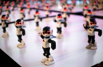 A total of 100 bodies of Robi prefabricated humanoid robot perform in a group during a promotional event of the third edition launch of its DIY weekly magazine that comes with the robot kits in Tokyo Tuesday, Jan. 20, 2015. The 34-centimeter (13.4-inch) tall robot, that can recognize more than 200 Japanese phrases, walk, dance and kick a ball, will be fully assembled with 70 volumes of the magazine. (AP Photo/Eugene Hoshiko)