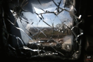 The town of Sinjar is seen through a bulletproof window damaged by sniper fire from Sunni extremist fighters of the Islamic State group at a viewpoint in a Peshmerga base on the frontline with the extremists, near Sinjar, Iraq, Monday Jan. 12, 2015. Kurdish forces have taken back a large part of the town of Sinjar since the Sunni extremists occupied it in August last year. (AP Photo/Bram Janssen)
