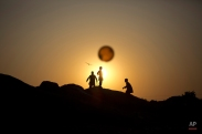 Afghan refugee children chase a balloon on the outskirts of Islamabad, Pakistan, Friday, Jan. 16, 2015. (AP Photo/Muhammed Muheisen)