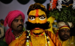 An artist from the state of Telangana reacts to the camera as they wait for their turn to perform during a media preview displaying a glimpse of culture of different parts of India, in New Delhi, India, Thursday, Jan. 22, 2015. The tableaux will be part of the Indian Republic Day parade on Jan. 26. (AP Photo/Altaf Qadri)