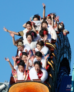 Kimono-clad women, who reach the age of 20 this year, ride a roller coaster following their Coming of Age ceremony at Tokyo's Toshimaen amusement park on the Coming of Age Day national holiday in Tokyo, Monday, Jan. 12, 2015. The event was hosted by the amusement park to celebrate the coming of age for the participants. (AP Photo/Shizuo Kambayashi)
