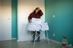 Cecilia Paredes puts her hand to her head, while she takes care of her baby inside an empty room as riot police surround the apartment during her and her family's eviction in Madrid, Spain, Friday, Jan. 23, 2015. Paredes, 43, and her unemployed electrician husband Wilson Ruilova, 35, both from Ecuador, have three children: Dilan, a baby born less than two months ago; Andres, 16, and Miguel, seven. They have been unable to pay their rent after she lost her job as an elderly care assistant two years ago. The government company that owned the apartment sold it last year to an investor group along with more than 1,800 other apartments built for the needy and the new owner sought the family's eviction. (AP Photo/Andres Kudacki)