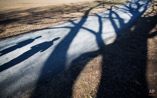 Joggers cast shadows along with trees lining a running track in Piedmont Park, Friday, Jan. 16, 2015, in Atlanta. Drizzly and foggy weather all week gave way to sunny skies Friday with temperatures expected to reach the low 50s and hover around the mid 50s through the weekend. (AP Photo/David Goldman)