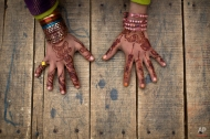 An Afghan refugee schoolgirl displays her hands decorated with Bangles and painted with Henna paste during class at a makeshift school on the outskirts of Islamabad, Pakistan, Monday, Jan. 12, 2015. Pakistani children and staff returned to a school in northwestern Pakistan where Taliban gunmen nearly a month ago killed 150 people almost all of them students. (AP Photo/Muhammed Muheisen)