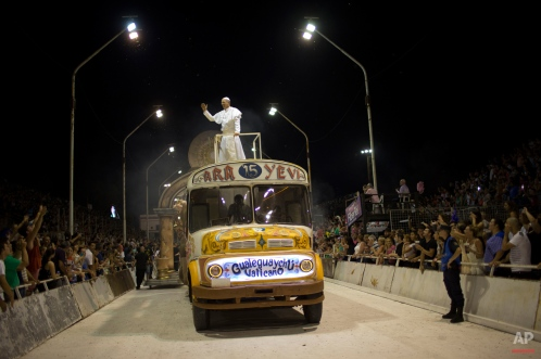 Roman Figun, a local lawyer, performs the role of Pope Francis with the Ara Yevi samba school as he stands on a bus representing his humble arrival to the Vatican during carnival celebrations in Gualeguaychu, Argentina, early Sunday, Jan. 11, 2015. Ara Yevi, one of the three samba schools performing this year, used Pope Francis as their central theme. Figun says he does his best to play the Pope and his carnival group wants to spread his message. (AP Photo/Natacha Pisarenko)