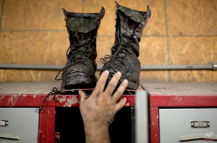 In this Oct. 15, 2014 photo, coal miner Johnny Turner, 35, puts his coal boots on top of his locker after finishing a shift underground at the Perkins Branch coal mine in Cumberland, Ky. (AP Photo/David Goldman)