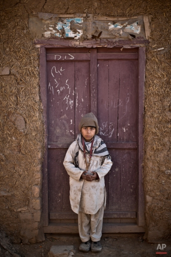 Afghan refugee, Hamza Gul, 11, poses for a picture while playing with his slingshot, wrapped around his neck, in a slum on the outskirts of Islamabad, Pakistan, Friday, Jan. 30, 2015. (AP Photo/Muhammed Muheisen)