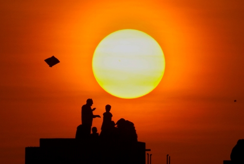 Indians fly kites standing on the roof of a building on the eve of Makar Sankranti, a Hindu harvest festival, also known as kite festival, in Ahmadabad, India, Tuesday, Jan. 13, 2015. Kites are flown in many parts of India during Makar Sankranti, a festival that marks the transition of winter to spring. (AP Photo/Ajit Solanki)