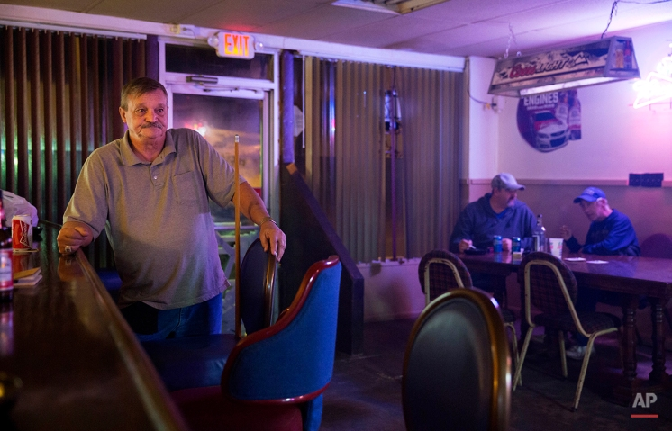 """In this Oct. 19, 2014 photo, former coal miner Tommy Walters, 66, waits his turn while playing pool in his bar, one of only two still operating in the area in Cumberland, Ky. Walters, a 17-year coal mine veteran, had left home numerous times over the years looking for work out of state as the opportunities for coal miners at home fluctuated. """"It bothers you, it hurts you that one time this town was booming,"""" said Walters. """"If I knew back then what this town would be like today, I never would have come back."""" (AP Photo/David Goldman)"""