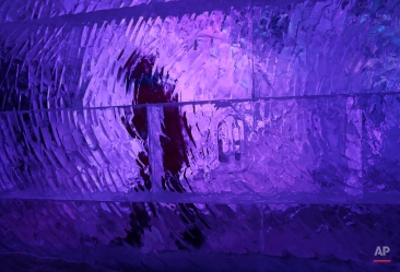 A boy walks behind an ice wall, at the annual ice sculpture festival in Bruges, western Belgium, Monday, Dec. 29, 2014. This year's theme is titled 'the Land of the Hobs', and takes visitors into the mythology of dwarves, elves, fairies, hunters, magicians and devilish figures. (AP Photo/Yves Logghe)