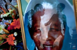 A mother, right, walks to have a family photograph taken with her son, center, seen reflected in a portrait of Nelson Mandela, outside the Mediclinic Heart Hospital where former South African President Nelson Mandela is being treated in Pretoria, South Africa Monday, July 8, 2013. (AP Photo/Ben Curtis)