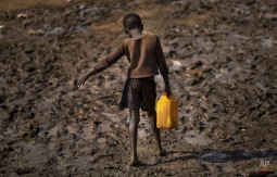 A displaced child struggles to carry a container of drinking water obtained from a truck across a slippery muddy patch of ground at a United Nations compound which has become home to thousands of people displaced by the recent fighting, in the capital Juba, South Sudan Sunday, Dec. 29, 2013. (AP Photo/Ben Curtis)