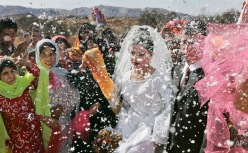 Villagers spray the groom, Mohammed Zamanpour, 25, and his bride Manijeh, 16, with foam confetti at a Bakhtiari nomad wedding in the mountain village of Abid near the town of Masjid-e-Soleiman in southwestern Iran, Thursday, Nov. 29, 2007. (AP Photo/Ben Curtis)