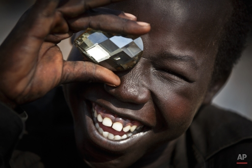 A displaced boy mimics the photographer taking a picture of him, using a fake plastic jewel, at a United Nations compound which has become home to thousands of people displaced by the recent fighting, in the capital Juba, South Sudan Sunday, Dec. 29, 2013. (AP Photo/Ben Curtis)