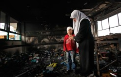 In this photo taken Monday, Jan. 19, 2009, Fatma Zidane El-Banneh, 8, and her mother Azza are pictured after returning from the hospital to the Beit Lahiya Elementary Co-educational school, where Azhar said Fatma was burned by white phosphorus, which could not be independently verified, in Beit Lahiya, in the northern Gaza strip. (AP Photo/Ben Curtis)