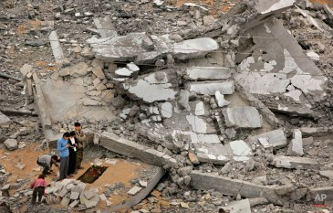 Palestinians offer traditional Muslim Friday prayers amidst the rubble of a destroyed mosque, where only the minaret still stands, in Beit Lahiya in the Gaza strip, Friday, Jan. 23, 2009. (AP Photo/Ben Curtis)