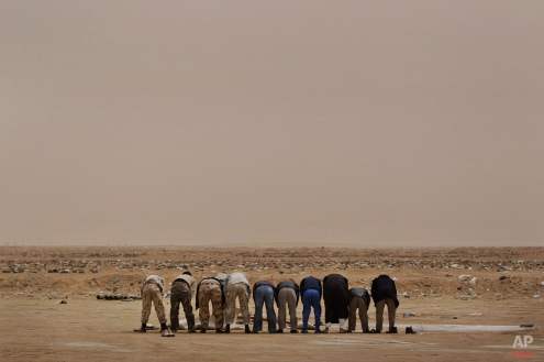 Libyan rebel fighters pray in the desert on hearing claims from other rebels that an airstrike further up the road towards Brega had hit rebel forces killing at least two and injuring more than a dozen, at the west gate of Ajdabiya, Libya Thursday, April 7, 2011. (AP Photo/Ben Curtis)