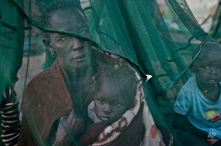 One of the few to have a mosquito net, a displaced family who fled the recent fighting between government and rebel forces in Bor by boat across the White Nile, sit under it after waking up in the morning in the town of Awerial, South Sudan Thursday, Jan. 2, 2014. (AP Photo/Ben Curtis)