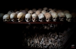 The skulls and bones of some of those who were slaughtered as they sought refuge inside the church, are laid out on shelves in an underground vault as a memorial to the thousands who were killed in and around the Catholic church during the 1994 genocide in Nyamata, Rwanda, Friday, April 4, 2014. (AP Photo/Ben Curtis)
