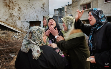 A Palestinian woman from the Suboh family weeps as she is comforted after learning the body of a releative was dug out of the rubble of a house destroyed in recent days in Israeli bombardment in Beit Lahiya, northern Gaza strip, Monday, Jan. 19, 2009. (AP Photo/Ben Curtis)