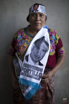 """Eliseth Cocon, wearing a scarf decorated with a portrait of former Guatemalan President Alfonso Portillo that reads in Spanish: """"Welcome Portillo, we trust in you,"""" poses for a portrait as she waits for Portillo to land at the La Aurora airport in Guatemala City, Wednesday, Feb. 25, 2015. Portillo, who was sentenced to nearly six years in prison for accepting $2.5 million in bribes from Taiwan, was released Wednesday from a U.S. prison and is returning to his home country. (AP Photo/Luis Soto)"""