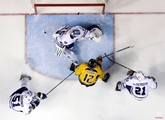 Nashville Predators forward Mike Fisher (12) scores a goal against Toronto Maple Leafs goalie Jonathan Bernier (45) in the third period of an NHL hockey game, Tuesday, Feb. 3, 2015, in Nashville, Tenn. Also defending for the Maple Leafs are Jake Gardiner (51) and James van Riemsdyk (21). (AP Photo/Mark Humphrey)