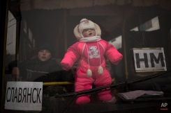 A baby is held at the window of a bus with people waiting to leave the town of Debaltseve, eastern Ukraine, Friday, Feb. 6, 2015. At left is a sign reading Slovyansk. Pro-Russia rebels and the Ukrainian authorities agreed Friday on a humanitarian corridor to evacuate civilians from the epicenter of fighting in eastern Ukraine as German and French leaders prepared to bring their peace plan to Moscow. (AP Photo/Evgeniy Maloletka)