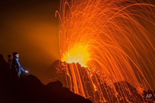 A person looks at the Piton de la Fournaise volcano in eruption, Thursday, Feb. 5, 2015, in the French Indian Ocean island of La Reunion. This is the second eruption in the past year at Piton de la Fournaise after 3-years of quiet. (AP Photo/Fabrice Wislez)