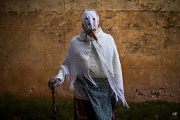 A reveler wearing a costume poses for a picture during a traditional carnival celebration in the small village of Luzon, Spain, Saturday, Feb. 14, 2015. Preserved records from the 14th century document Luzon's carnival, but the real origin of the tradition could be much older. Carnival festivals are celebrated in their own way around hundreds of villages in Spain. (AP Photo/Andres Kudacki)