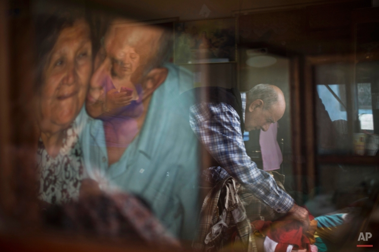 """In this Feb. 7, 2015 photo, veteran clown Ricardo Farfan, popularly known as """"Pitito,"""" is reflected in a glass case as he prepares his clown costume for his 91st birthday celebration at his home in Lima, Peru. (AP Photo/Esteban Felix)"""