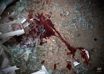 Pieces of broken glass and blood on the ground in clinic 27, damaged after shelling, in Donetsk, Ukraine, Wednesday, Feb. 4, 2015. Heavy shelling in the rebel stronghold of Donetsk in eastern Ukraine on Wednesday afternoon killed at least five people and damaged a hospital, six schools and five kindergartens, local officials said. (AP Photo/Vadim Braydov)