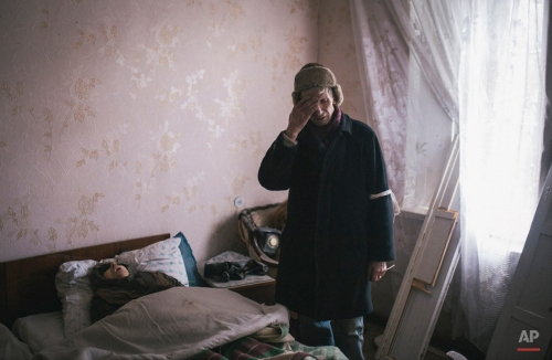 An elderly man stands next to the body of his wife, who died of an apparent heart attack after an ambulance was unable to make its way through fighting, in the town of Vuhlehirsk, eastern Ukraine, Tuesday, Feb. 10, 2015. Fighting in eastern Ukraine intensified on Tuesday ahead of much-anticipated peace talks, with both sides claiming significant advances. (AP Photo/Vadim Braydov)