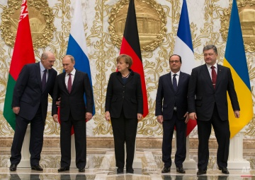 Belarusian President Alexander Lukashenko, left, speaks to Russian President Vladimir Putin, second left, as German Chancellor Angela Merkel, center, French President Francois Hollande, second right, and Ukrainian President Petro Poroshenko come to pose for a photo during a time-break in their peace talks in Minsk, Belarus, Wednesday, Feb. 11, 2015. Leaders of Russia, Ukraine, France and Germany are gathering for crucial talks in the hope of negotiating an end fighting between Russia-backed separatist and government forces in eastern Ukraine. (AP Photo/Alexander Zemlianichenko)