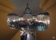 A rally called 'Patriotic Europeans against the Islamization of the West' (PEGIDA) is photographed through a gap of a balcony with the view to the Frauenkirche cathedral (Church of Our Lady) while the exterior lighting was switched off in Dresden, eastern Germany, Monday, Feb. 9, 2015. (AP Photo/Jens Meyer)