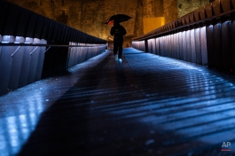 A man shelters from the rain under an umbrella while crossing a bridge, in Pamplona northern Spain, Monday, Feb. 23, 2015. The bridge connects the old city with the new city. (AP Photo/Alvaro Barrientos)