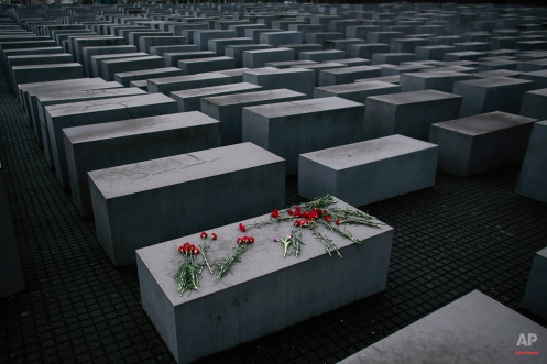 Flowers lie on a concrete slab of the Holocaust Memorial to mark the International Holocaust Remembrance Day and commemorating the 70th anniversary of the liberation of the Nazi Auschwitz death camp in Berlin, Tuesday, Jan. 27, 2015. (AP Photo/Markus Schreiber)