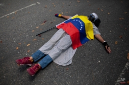 A protester covered by the Venezuelan flag lies on the ground during a protest against violence outside the Vatican's diplomatic mission in Caracas, Venezuela, Wednesday, Feb. 25, 2015. Protesters gathered here to ask Pope Francis to intervene after the death of a 14-year-old boy who was shot in the head Tuesday at an anti-government protest in the city of San Cristobal. (AP Photo/Ariana Cubillos)